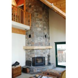 An RSF Delta efficient wood fireplace finished by Friendly Fires in a corner with stone.