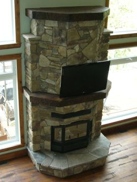 This efficient large glass wood fireplace has a flat screen TV installed above it.