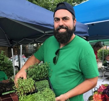 Photo of Ross Outten holding microgreens at a farmers market
