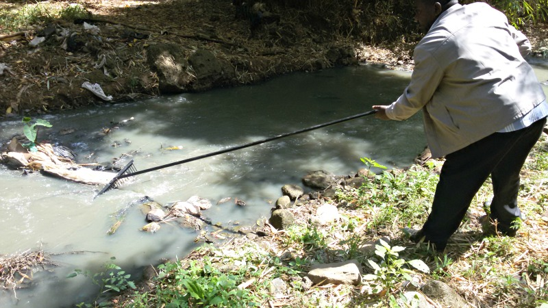Mr. Mwai, County Staff at the Park, testing out the custom made rake to pull rubbish from the river