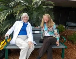 Angie Zerad, who donated a garden bench for the Elsie Quirk Library new Reading Garden, relaxed with Becky Dubowik after the Grand Opening Ceremony on February 28.