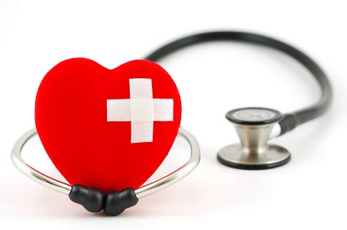 Image shows a stethoscope and a heart shaped balloon with a white cross on it indicating a Medical concept.