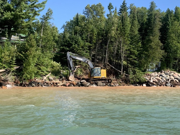 An excavator operator moves the boulders into place