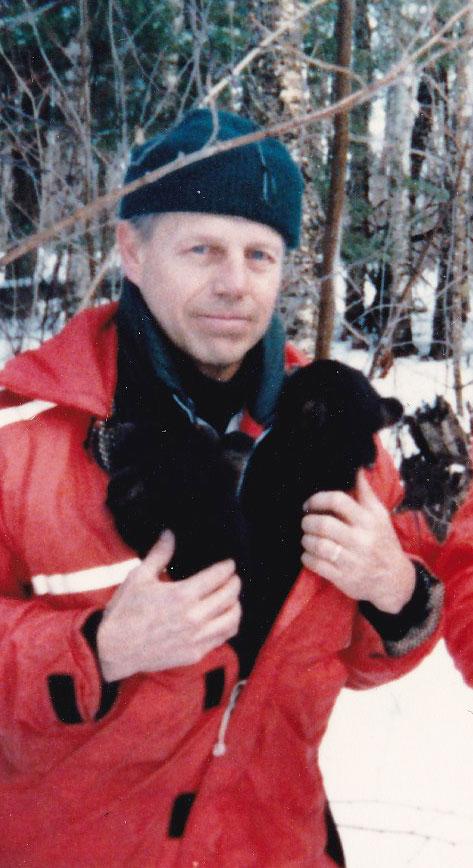 Tom Bredow keeping bear cubs warm in his jacket on Stockton Island
