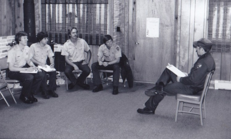 Dave Chesky sitting in the Little Sand Bay visitor center during seasonal training in 1979 listening to ranger Jeff Hepner