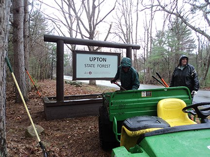 Clearing leaves near the Upton State Forest sign