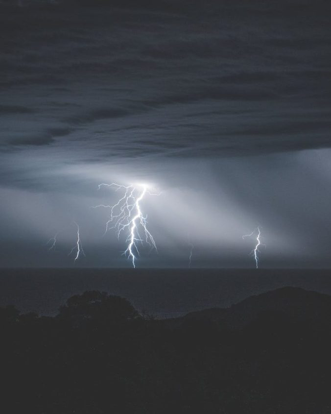 bright lightnings with rainy clouds over ocean