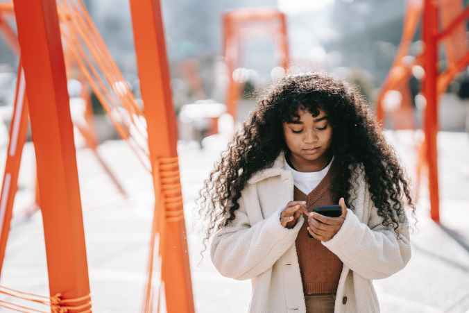focused black woman using smartphone on sunny spring street