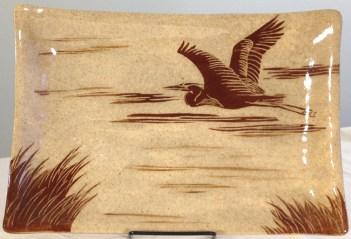 Stoneware platter, sgraffito carved heron in flight