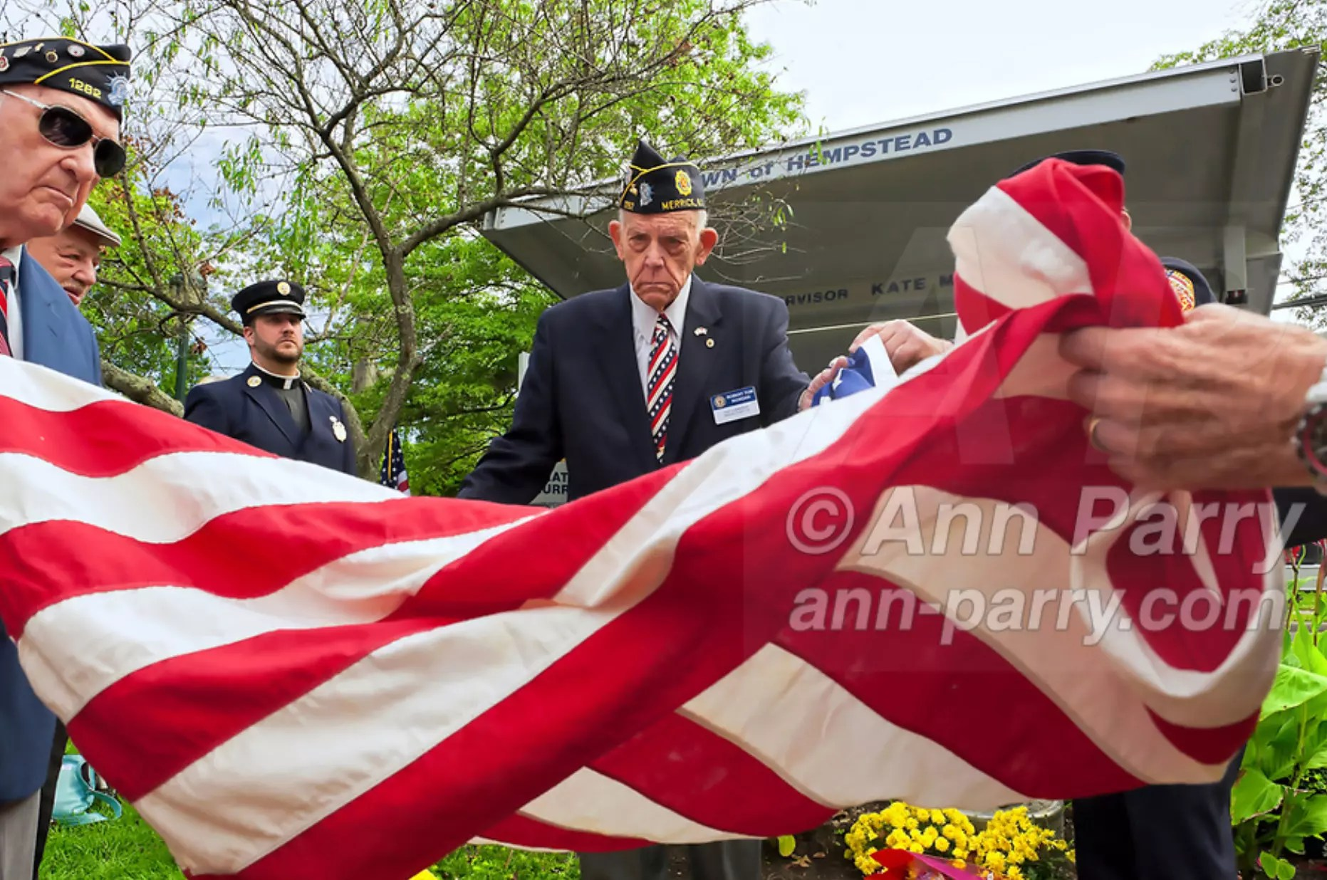 Merrick, NY, USA. Sept. 11, 2011. Removing American Flag to reveal monument made with steel from World Trade Center, at Merrick Post #1282 American Legion Tenth Anniversary of 9/11 event are, L-R, Rabbi Paul Kirchner, Father Eric Fasano, (center) Adjutant Robert Tom Riordan PCC.