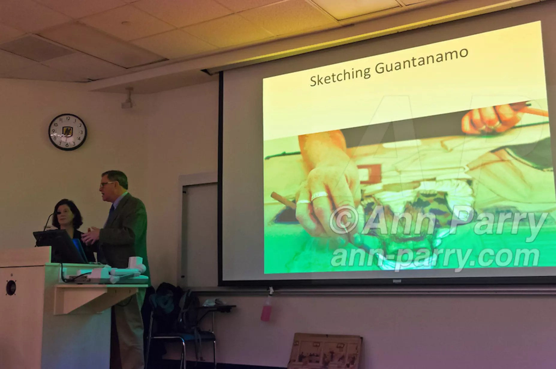 "Hempstead, NY, U.S. 12th Nov. 2013. Asst. Prof. DANIEL VAN BENTHUYSEN introduces JANET HAMLIN, a courtroom artist covering the military tribunals at Guantanamo Bay since 2006, who showed her drawings and discussed her work at Hofstra University. Much of the time she was only journalist providing a visual record of events at the U.S. naval base in Cuba, and her new book ""Sketching Guantanomo"" is a collection of her images."