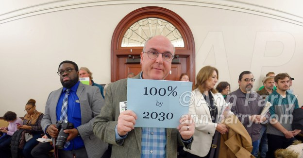 Mineola, New York, USA. 15th Feb, 2019. ERIC WELTMAN, Brooklyn, a Senior Organizer for Food & Water Watch in New York, is holding a blue card with 100% by 2030 on it, referring to goal of 100% clean energy by 2030, during NYS Senate Public Hearing on Climate, Community & Protection Act, Bill S7253, sponsored by Sen. Kaminsky, Chair of Senate Standing Committee on Environmental Conservation. This 3rd public hearing on bill to fight climate change was on Long Island.