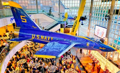 Garden City, New York, U.S. June 6, 2019. On stage are (at lectern) MICHAEL STROMER, JetBlue Chief Product Officer, Techology; and MARC MACDONNELL, Chair, Board of Directors of Cradle of Aviation, as seen from third level of atrium of CAM, during Apollo at 50 Anniversary Dinner, an Apollo astronaut tribute celebrating the Apollo 11 mission Moon landing. U.S. Navy Blue Angels Grumman F-11A Tiger jet is suspended from ceiling. Astronauts and Nassau County Executive Laura Curran, are seated at tables next to stage.