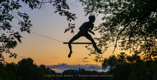 "Old Westbury, NY, U.S., Sept. 1, 2019. ""Athlete 1 - Over the Hurdle"" seen silhouetted by sky at upper right, is one of 33 outdoor sculptures by Jerzy Kedziora (Jotka), b. 1947 in Poland, and his Balance in Nature art is on view at historic Old Westbury Gardens in Long Island, until October 13, 2019."