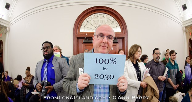 Mineola, New York, USA. 15th Feb, 2019. ERIC WELTMAN, Brooklyn, a Senior Organizer for Food & Water Watch in New York, is holding a blue card with 100% by 2030 on it, referring to goal of 100% clean energy by 2030, during NYS Senate Public Hearing on Climate, Community & Protection Act, Bill S7253, sponsored by Sen. Kaminsky, Chair of Senate Standing Committee on Environmental Conservation. This 3rd public hearing on bill to fight climate change was on Long Island. © 2019 Ann Parry, AnnParry.com