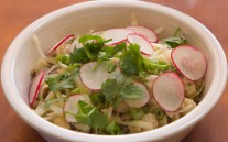 A bowl of posole hidden by all the condiments