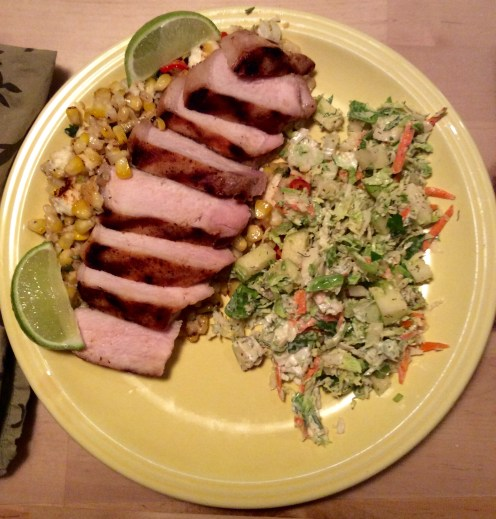 Grilled pork chop on bed of esquites with Brussels sprout slaw