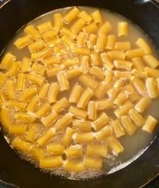 Rigatoni cooking in fish stock
