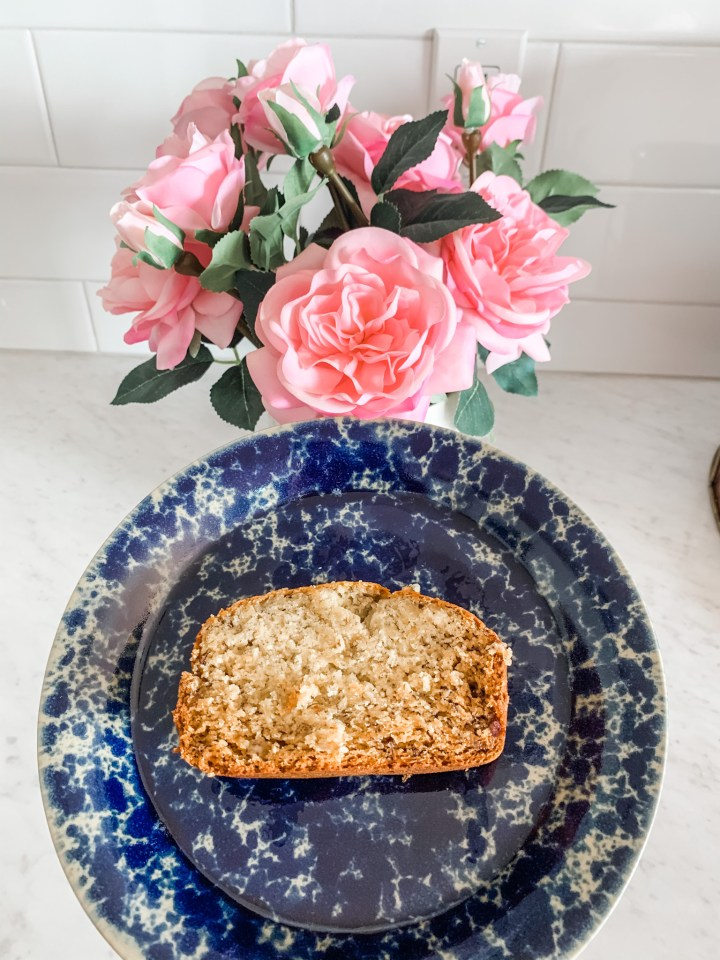 Gluten free banana bread on a blue plate with a pink flower