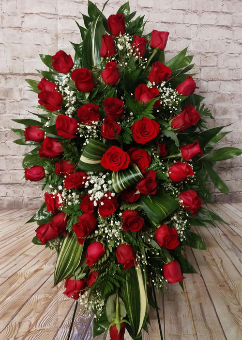 Standing sympathy spray of red roses and babies breath