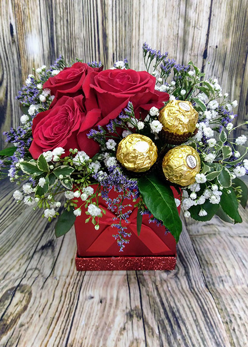 Valentine's Day bouquet of roses and chocolate in red box. From the Heart Florist