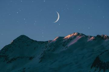 photo of the crescent moon over the mountains