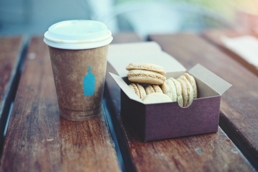 macaroons in a purple box, cofee in a recyclable cup on a wooden table