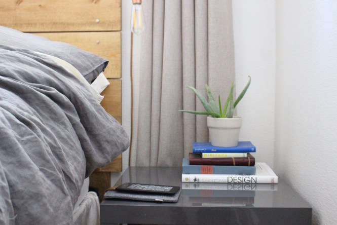Gray Ikea lack bedside table, books, succulent, linen curtains and duvet