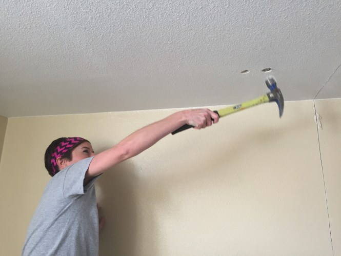 Kelly punching holes into ceiling demo