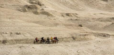 A caravan of ponies moves across the barren landscape; Lo Manthang
