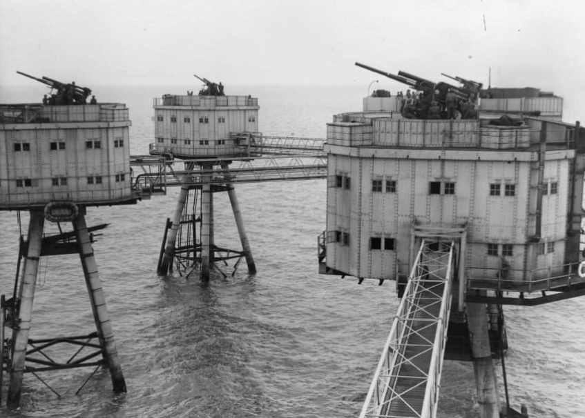 A contemporary image of the sea forts with tubular steel walkways and 3.7in HAA guns clearly visible, and manned. What is interesting is what appears to be an inflatable raft tied to the side of the left most tower.