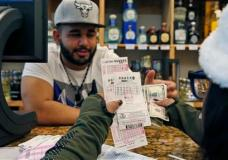 Samir Akhter, the owner of Penn Branch Liquor, exchanges money for Powerball tickets, Saturday, Jan. 9, 2016 in Washington.  Officials say it's increasingly likely that someone will win the $900 million Powerball jackpot, which grew by $100 million just hours before Saturday night's drawing.   (AP Photo/Alex Brandon)