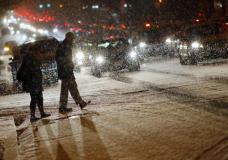 People cross a street as it snows in Washington, January 20, 2016. REUTERS/Carlos Barria