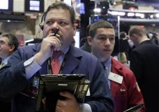 Trader John Santiago, foreground left, works on the floor of the New York Stock Exchange, Monday, Feb. 1, 2016. Another steep drop in oil and natural gas prices is pulling the stock market lower in early trading. (AP Photo/Richard Drew)