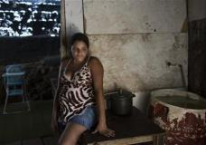 Leydiane da Silva, who's eight months pregnant, rests next to a water storage container, a potential mosquito breeding site, inside her home which stands on stilts above water, trash and sewage, in a slum in Recife, Pernambuco state, Brazil, Monday, Feb. 1, 2016. Zika is spread by the Aedes aegypti mosquito, which is well-adapted to humans, thrives in people's homes and can breed in even a bottle cap's-worth of stagnant water. While anyone can be bitten by Aedes, public health experts agree that the poor are more vulnerable because they often lack amenities that help diminish the risk, such as air conditioning and window screens. (AP Photo/Felipe Dana)