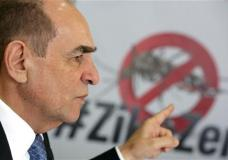 """Brazil's Health Minister Marcelo Castro speaks during an interview at the Health Ministry headquarters, in Brasilia, Brazil, Friday, Feb. 12, 2016. Castro made his remarks with a poster with an image of an Aedes aegypti mosquito and a text in Portuguese that reads """"One Mosquito is not stronger that a country."""" (AP Photo/Eraldo Peres)"""