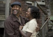 """This image released by Paramount Pictures shows Denzel Washington, left, and Viola Davis in a scene from, """"Fences."""" Adapting Wilson's masterpiece has taken more than 30 years. Washington, who directed the film and starred on Broadway revival of """"Fences"""" seven years ago, made some key decisions when he was first tapped to translate the play onto celluloid. He reunited five of the main actors; Viola Davis, Stephen McKinley Henderson, Russell Hornsby and Mykelti Williamson. (David Lee/Paramount Pictures via AP)"""
