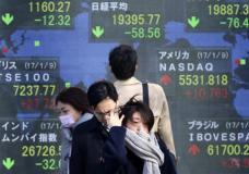 People wait to cross a street in front of an electronic stock board showing global stock market indexes at a securities firm in Tokyo, Tuesday, Jan. 10, 2017. Shares mostly fell in Asia on Tuesday, tracking losses on Wall Street apart from the Nasdaq composite index's fresh record high. (AP Photo/Shuji Kajiyama)
