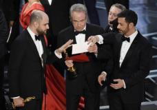 """""""La La Land"""" producer Jordan Horowitz, left, presenter Warren Beatty, center, and host Jimmy Kimmel right, look at an envelope announcing """"Moonlight"""" as best picture at the Oscars on Sunday, Feb. 26, 2017, at the Dolby Theatre in Los Angeles. It was originally announced mistakenly that """"La La Land"""" was the winner. (Photo by Chris Pizzello/Invision/AP)"""
