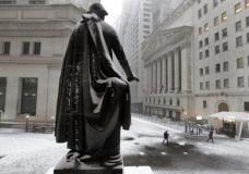 The statue of George Washington on the steps of Federal Hall overlooks the New York Stock Exchange, right, during a winter storm, Tuesday, March 14, 2017. Global stocks drifted lower on Tuesday as investors looked to the Federal Reserve's policy meeting for an expected interest rate increase and hints on future hikes. (AP Photo/Richard Drew)