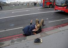 A woman assists an injured person after an incident on Westminster Bridge in London, Britain March 22, 2017.  REUTERS/Toby Melville