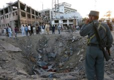 Security forces stand next to a crater created by massive explosion in front of the German Embassy in Kabul, Afghanistan, Wednesday, May 31, 2017. The suicide truck bomb hit a highly secure diplomatic area of Kabul killing scores of people and wounding hundreds more. (AP Photos/Rahmat Gul)