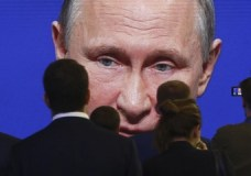 FILE PHOTO: Participants of the St. Petersburg International Economic Forum (SPIEF) gather near an electronic screen showing Russian President Vladimir Putin, who speaks during a session of the forum in St. Petersburg, Russia June 2, 2017. REUTERS/Sergei Karpukhin/File Photo - RTX397Z2