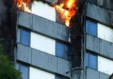 A person, bottom right, peers out of a window from a building on fire in London, Wednesday, June 14, 2017. Metropolitan Police in London say they're continuing to evacuate people from a massive apartment fire in west London. The fire has been burning for more than three hours and stretches from the second to the 27th floor of the building.(AP Photo/Matt Dunham)