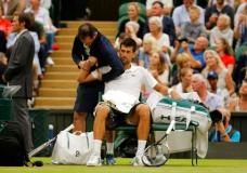 Serbia's Novak Djokovic receives treatment from a trainer during a break in his Men's Singles Match against Adrian Mannarino of France on day eight at the Wimbledon Tennis Championships in London Tuesday, July 11, 2017. (AP Photo/Alastair Grant)