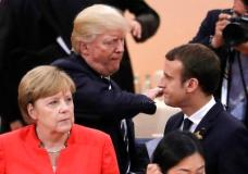 German Chancellor Angela Merkel, front, looks on as U.S. President Donald Trump, center, pads the shoulder of France's President Emmanuel Macron prior to the first working session on the first day of the G-20 summit in Hamburg, northern Germany, Friday, July 7, 2017. The leaders of the group of 20 meet July 7 and 8. (AP Photo/Markus Schreiber)