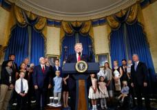 FILE - In this July 24, 2017, file photo, President Donald Trump, accompanied by Vice President Mike Pence, Health and Human Services Secretary Tom Price, and others, speaks about healthcare, in the Blue Room of the White House in Washington. A study by a nonpartisan group says the Trump administration's own actions are triggering double-digit premium increases on individual health insurance policies purchased by millions of consumers. (AP Photo/Alex Brandon, File)