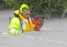 Wilford Martinez, right, is rescued from his flooded car by Harris County Sheriff's Department Richard Wagner along Interstate 610 in floodwaters from Tropical Storm Harvey on Sunday, Aug. 27, 2017, in Houston, Texas. (AP Photo/David J. Phillip)