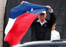 President Donald Trump holds up a Texas flag after speaking with supporters outside Firehouse 5  in Corpus Christi, Texas, Tuesday, Aug. 29, 2017, where he received a briefing on Harvey relief efforts. (AP Photo/Evan Vucci)