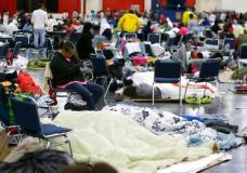 People rest at the George R. Brown Convention Center that has been set up as a shelter for evacuees escaping the floodwaters from Tropical Storm Harvey in Houston, Texas, Tuesday, Aug. 29, 2017. (AP Photo/LM Otero)